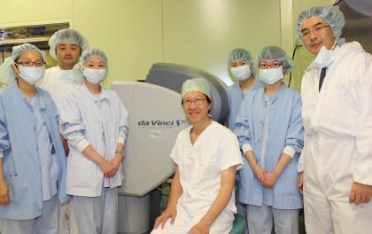 手術室のチームと。中央が手術用ロボットの「ダ・ヴィンチ」。「自分が執刀医でなくても手術室に入り、後輩をサポートすることがあります。手術中はあまり口出ししないようにしていますが……」と語る。